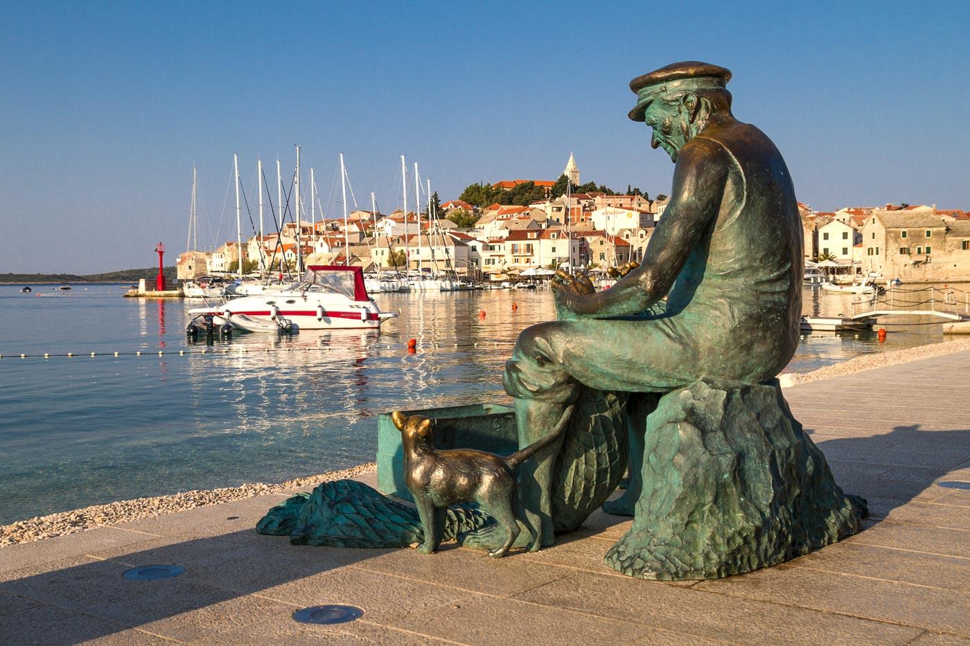 Скульптура рыбака на набережной. Примоштен, Хорватия